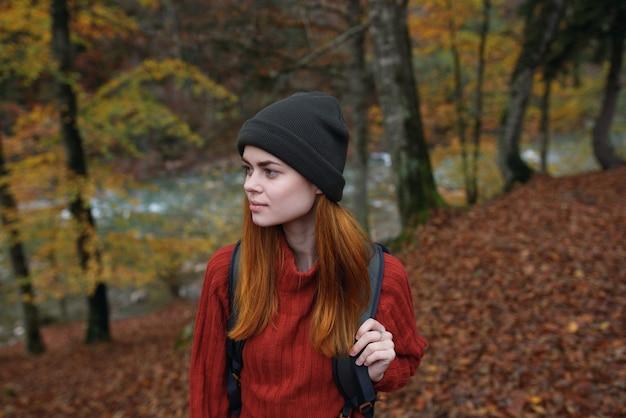Mulher alpinista caminha na floresta no outono na natureza perto do rio e deixa a paisagem