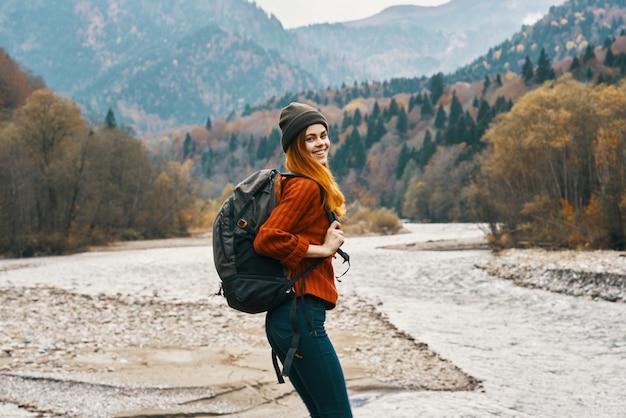 Mulher alpinista caminhando perto do rio, montanhas, viagens naturais