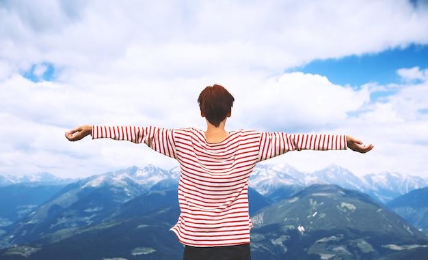 Mulher alpinista com braços erguidos e montanhas ao fundo viagem nas dolomitas, itália, europa