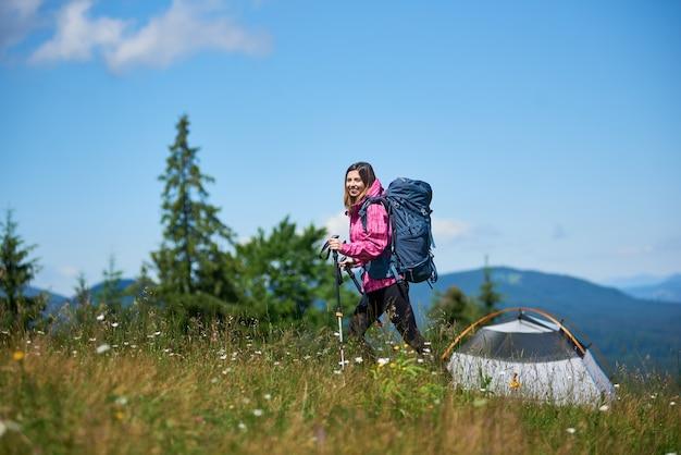 Mulher alpinista com mochila, caminhando nas montanhas
