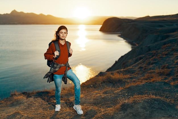Mulher alpinista com mochila nas férias de paisagem natural