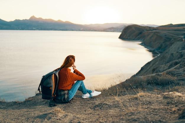 Mulher alpinista com mochila nas montanhas ao pôr do sol perto do mar