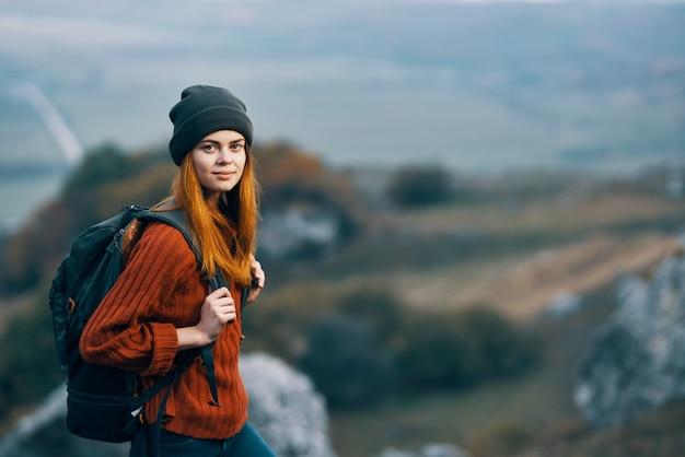 Mulher alpinista com mochila nas montanhas em uma aventura a pé