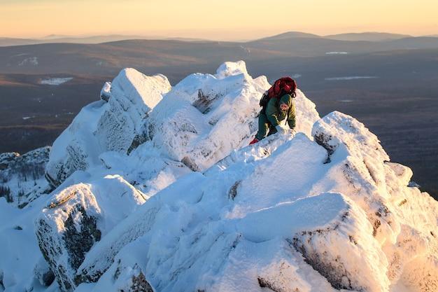 Mulher alpinista com mochila no topo da montanha passando por pedras e neve