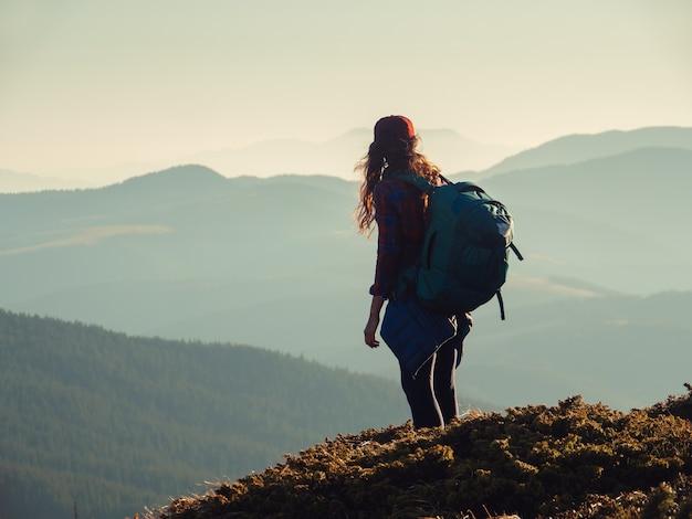 Mulher alpinista com mochila no topo de uma montanha com fundo de montanhas