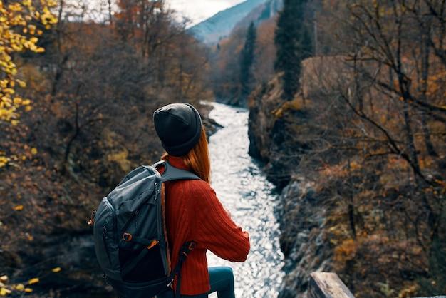 Mulher alpinista com mochila perto de rio, montanhas, outono, floresta, viagem