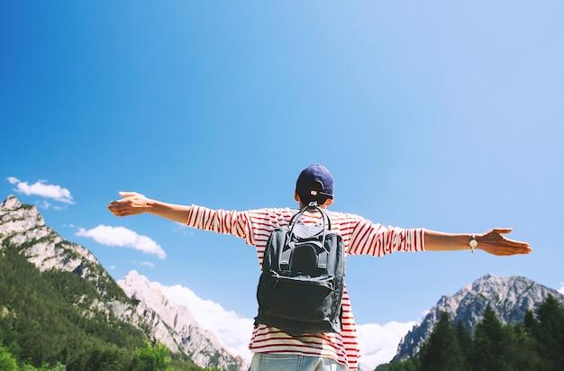 Mulher alpinista com os braços erguidos na vista traseira da natureza ao ar livre viagem nas dolomitas itália europa