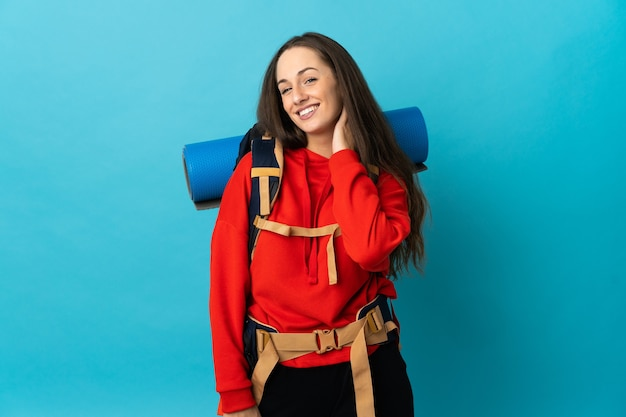 Mulher alpinista com uma grande mochila rindo sobre uma parede isolada