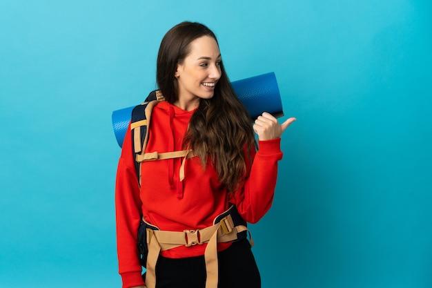 Mulher alpinista com uma grande mochila sobre uma parede isolada apontando para o lado para apresentar um produto