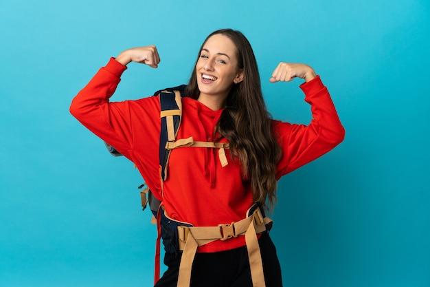 Mulher alpinista com uma grande mochila sobre uma parede isolada fazendo um gesto forte