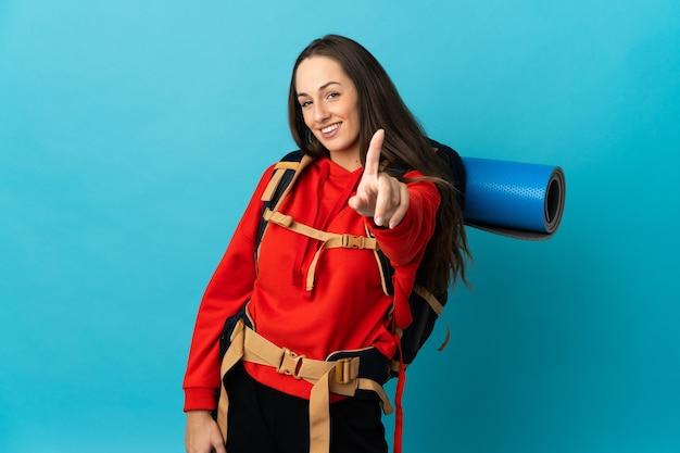 Mulher alpinista com uma grande mochila sobre uma parede isolada, mostrando e levantando um dedo
