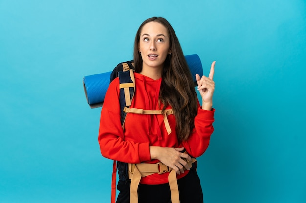 Mulher alpinista com uma grande mochila sobre uma parede isolada pensando em uma ideia apontando o dedo para cima