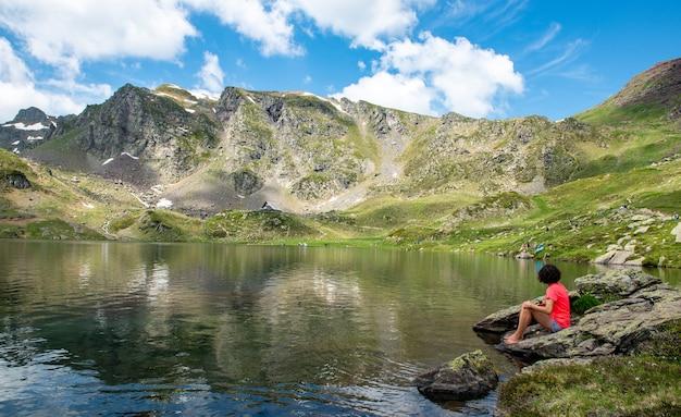 Mulher alpinista descansando perto de um lago na montanha