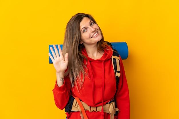 Mulher alpinista eslovaca com uma grande mochila isolada em um fundo amarelo e saudando com a mão em expressão feliz