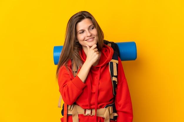 Mulher alpinista eslovaca com uma grande mochila isolada em um fundo amarelo, olhando para o lado e sorrindo