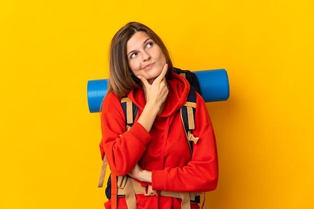 Mulher alpinista eslovaca com uma grande mochila isolada em um fundo amarelo, tendo dúvidas