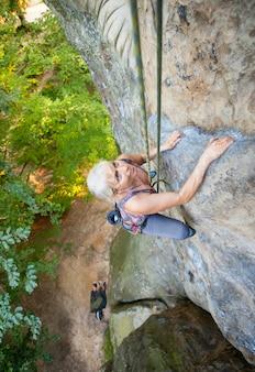 Mulher alpinista está subindo em uma parede rochosa