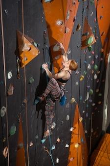 Mulher alpinista está subindo na parede de escalada indoor e olhando para cima