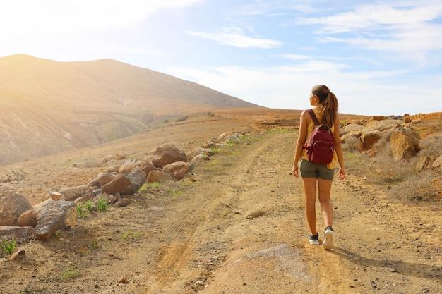 Mulher alpinista mochileira caminhando no caminho vendo o pôr do sol