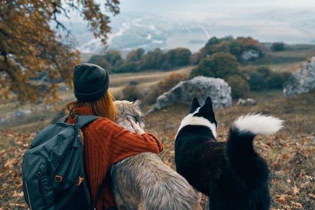 Mulher alpinista na natureza com cães, viagem de aventura