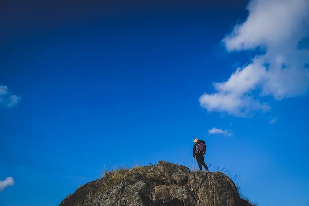 Mulher alpinista no penhasco de pedra contra o céu azul claro e nuvens
