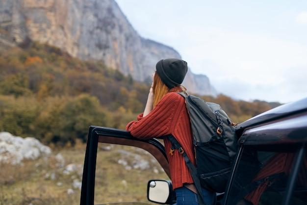 Mulher alpinista perto de carro na montanha, viagem de aventura
