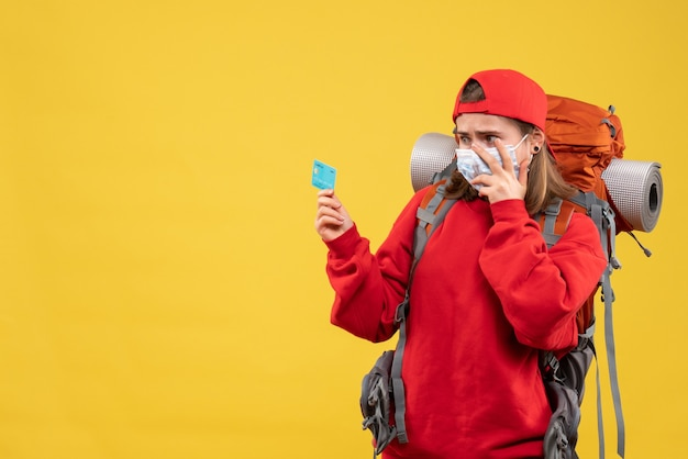 Mulher alpinista preocupada de frente com mochila e máscara segurando um cartão de descontos