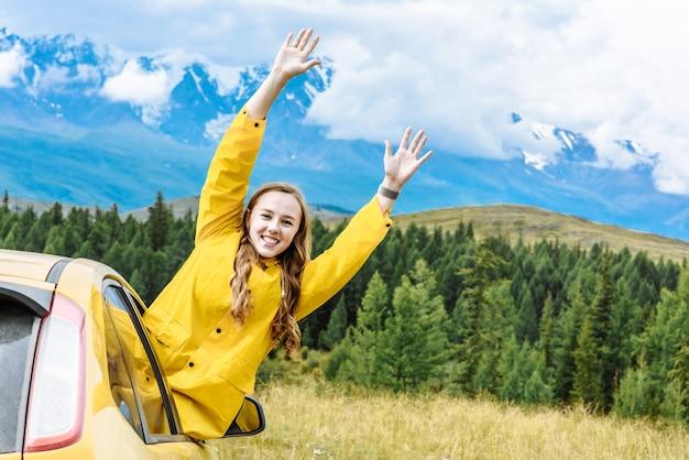 Mulher alpinista se inclinando alegremente para fora da janela do carro nas montanhas