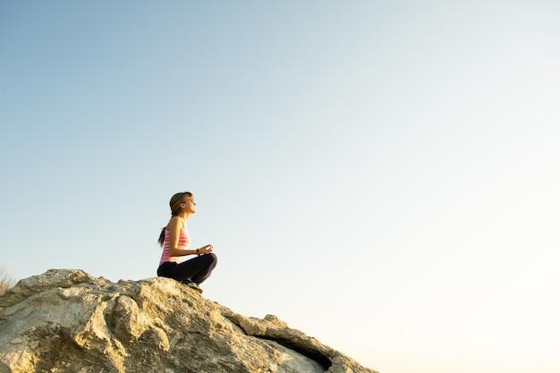 Mulher alpinista sentada em uma grande rocha íngreme, aproveitando o dia quente de verão
