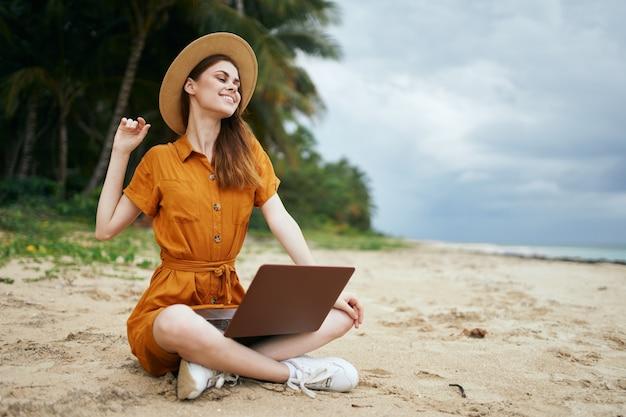 Mulher alpinista sentada na areia na praia com laptop viajando de férias