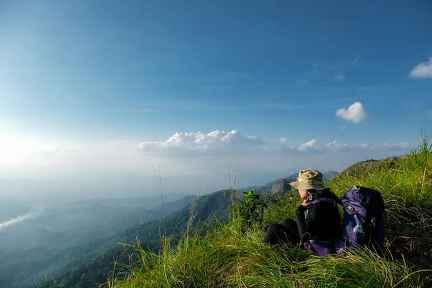 Mulher alpinista sentado na grama verde no penhasco da montanha