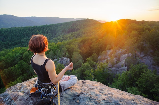 Mulher alpinista sentado protegido com corda e meditando
