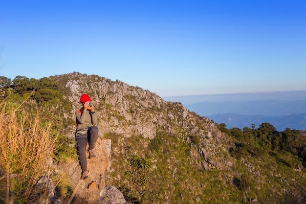 Mulher alpinista tirando foto com a câmera sem espelho na montanha. mochileiro fotos paisagem