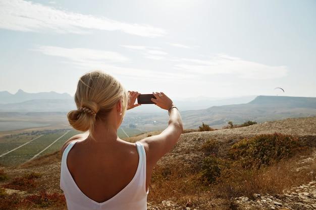 Mulher alpinista tirando foto com smartphone no pico da montanha