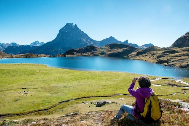 Mulher alpinista tirando foto do pic ossau, frança