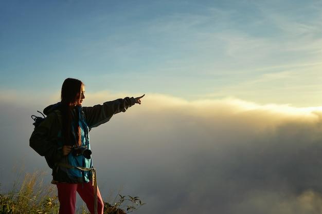 Mulher alpinista torcendo de braços abertos no pico da montanha