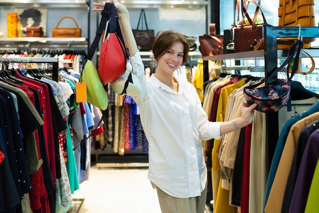 Mulher alta detém sacos de cinto colorido na sala de exposições
