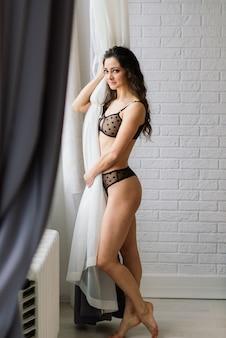 Mulher alta e esguia em lingerie sexy na atmosfera de natal.