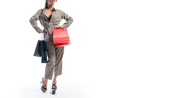 Mulher alta elegante posando com pacotes. sem nome. fundo branco. conceito de descontos, vendas, compras. mídia mista