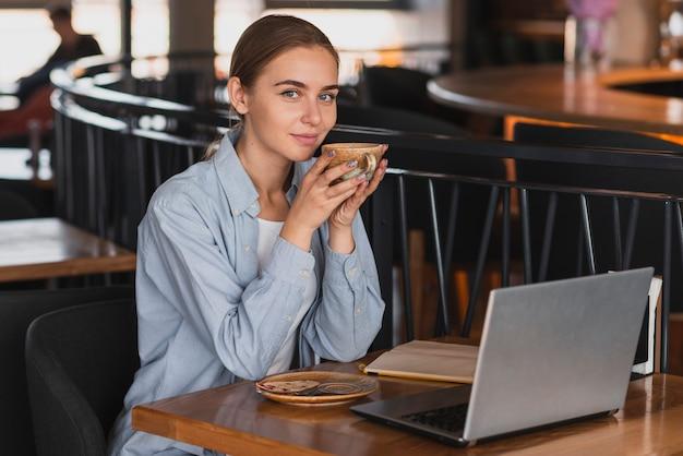Mulher alto ângulo, em, restaurante, bebendo café