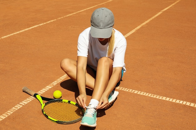 Mulher amarra cadarço na quadra de saibro com raquete e bola