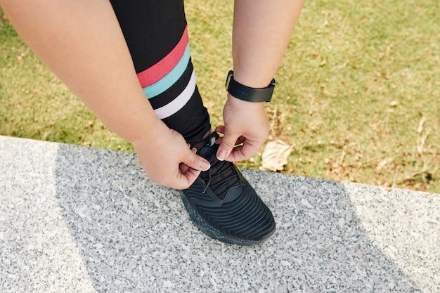 Mulher amarrando cadarços de sapato