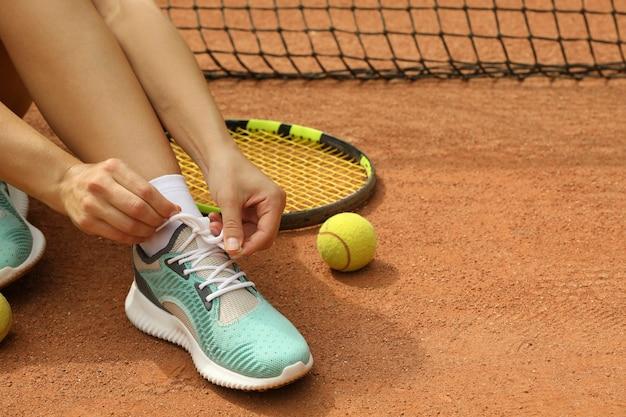 Mulher amarrando cadarços em quadra de saibro com raquete e bola de tênis