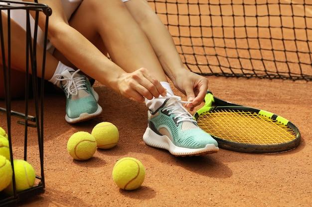 Mulher amarrando cadarços em quadra de saibro com raquete e bolas de tênis