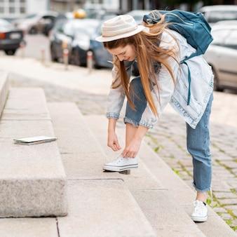 Mulher amarrando os sapatos nas escadas