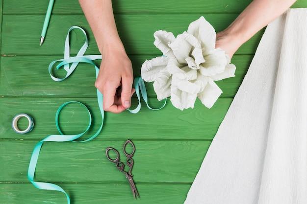 Mulher, amarrando, papel, flor, com, fita, contra, tabela madeira