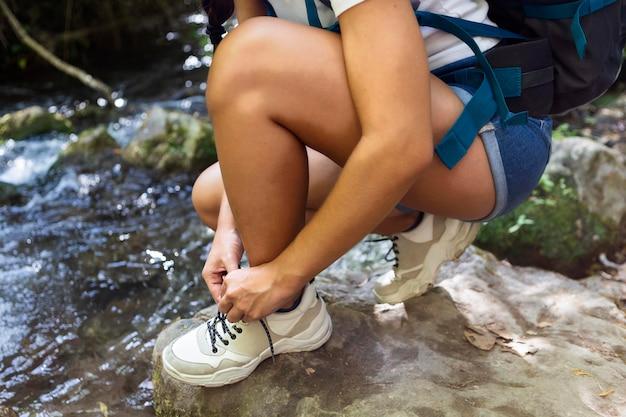 Mulher amarrando seus cadarços enquanto explora a natureza
