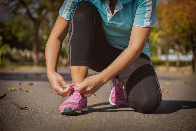 Mulher amarrando tênis de corrida, mulher de corredor de tênis amarrando cadarços para corrida de outono no parque florestal.