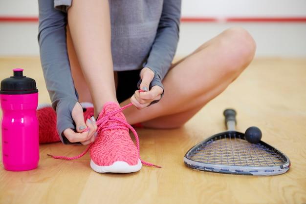 Mulher amarrando tênis esportivo na quadra