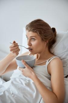 Mulher amável sentada na cama comendo mingau de leite, olhando para a frente